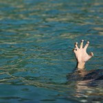 Man hand drowning in the ocean in a sunny day